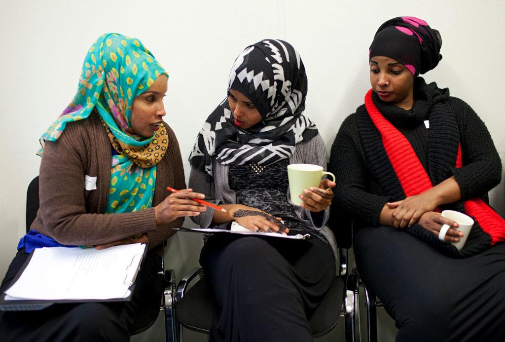 Kolme naista juttelemassa koulutuksessa
