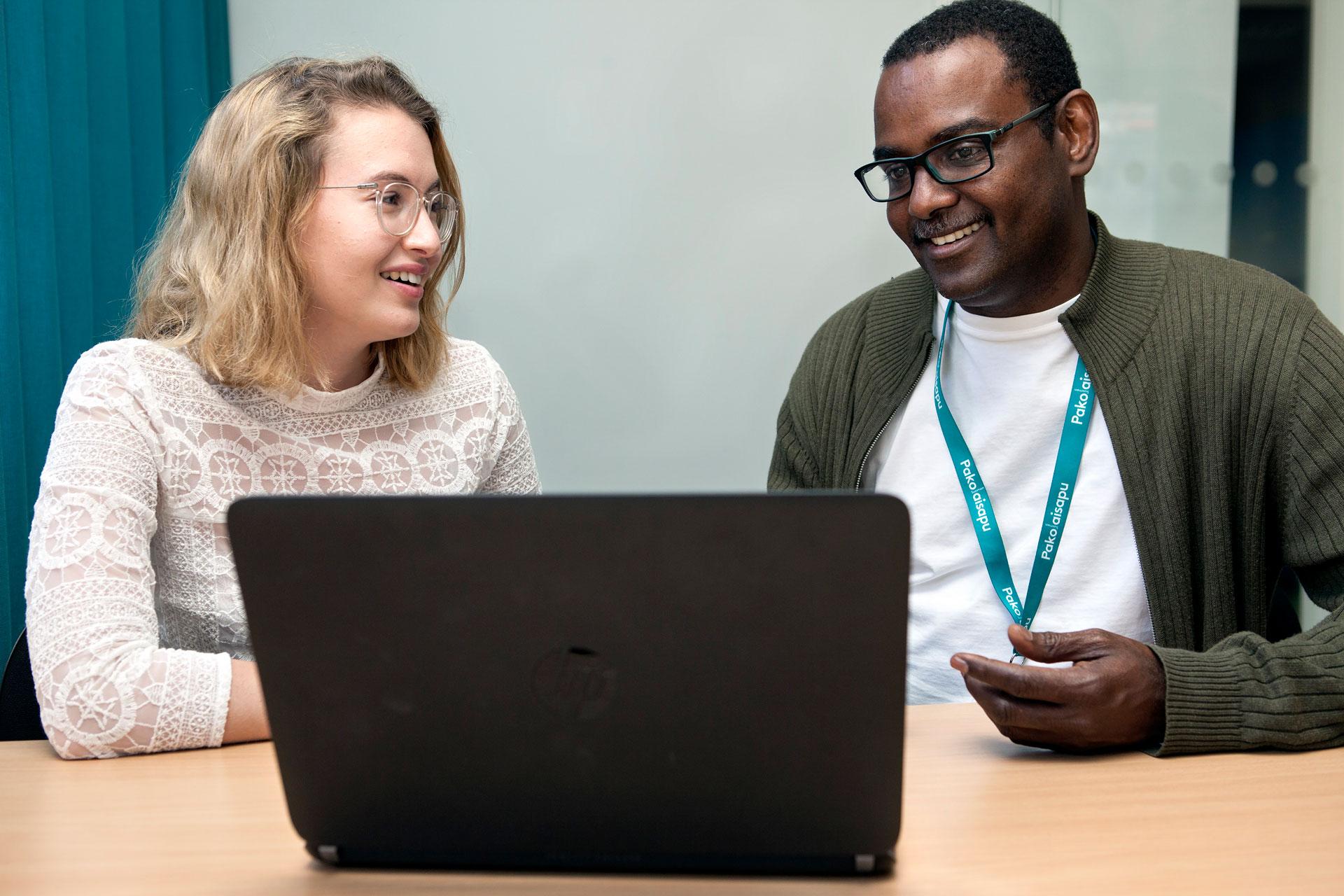 Hymyilevä nainen ja mies keskustelevat tietokoneen äärellä.