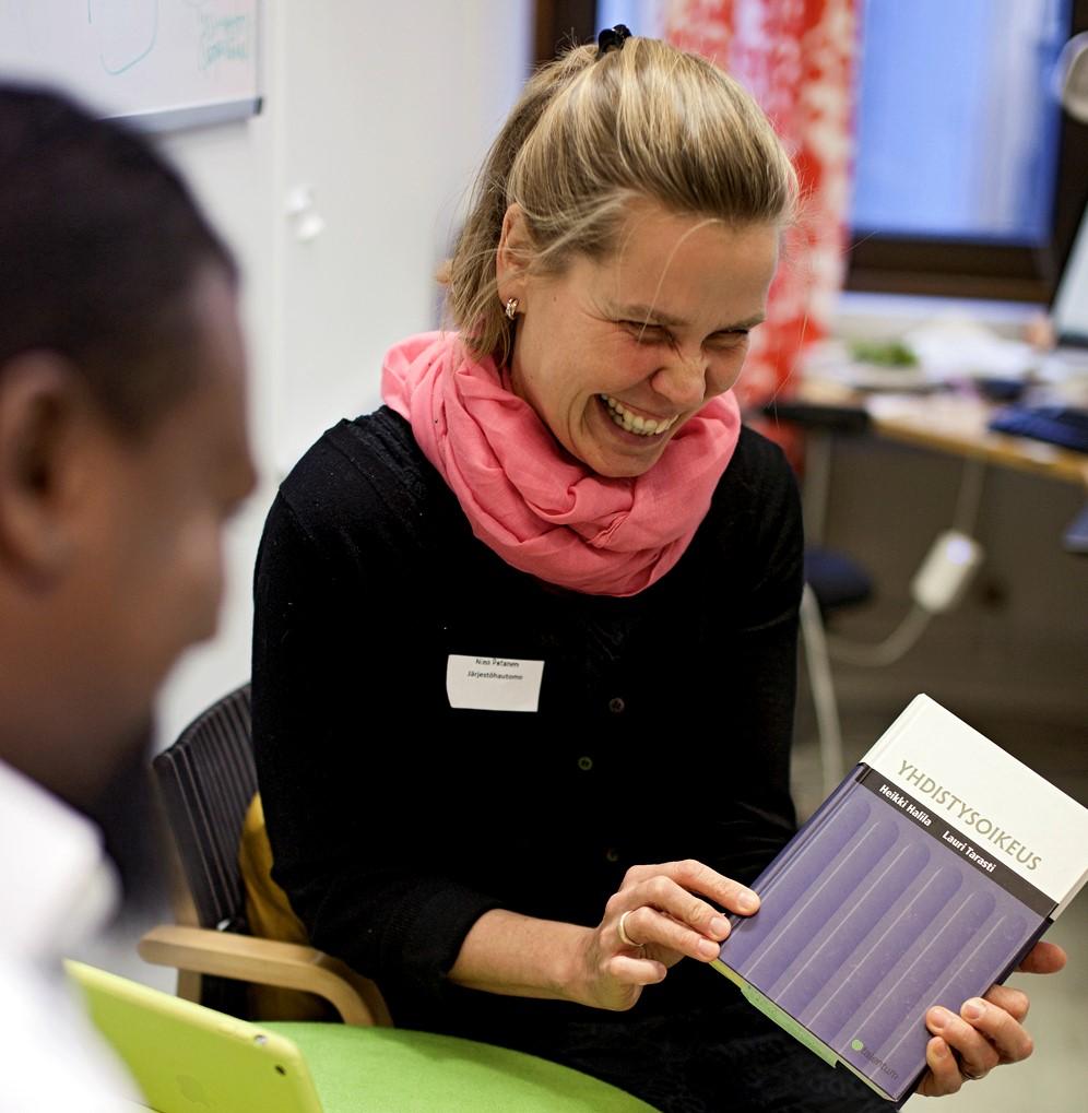 """Miksi tietosuoja on tärkeä aihe yhdistyksille? Kuvassa nainen koulutuksessa pitelee kädessään """"Yhdistysoikeus""""-kirjaa"""