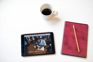 Kahvikuppi, vihko, kynä ja tabletti pöydällä.