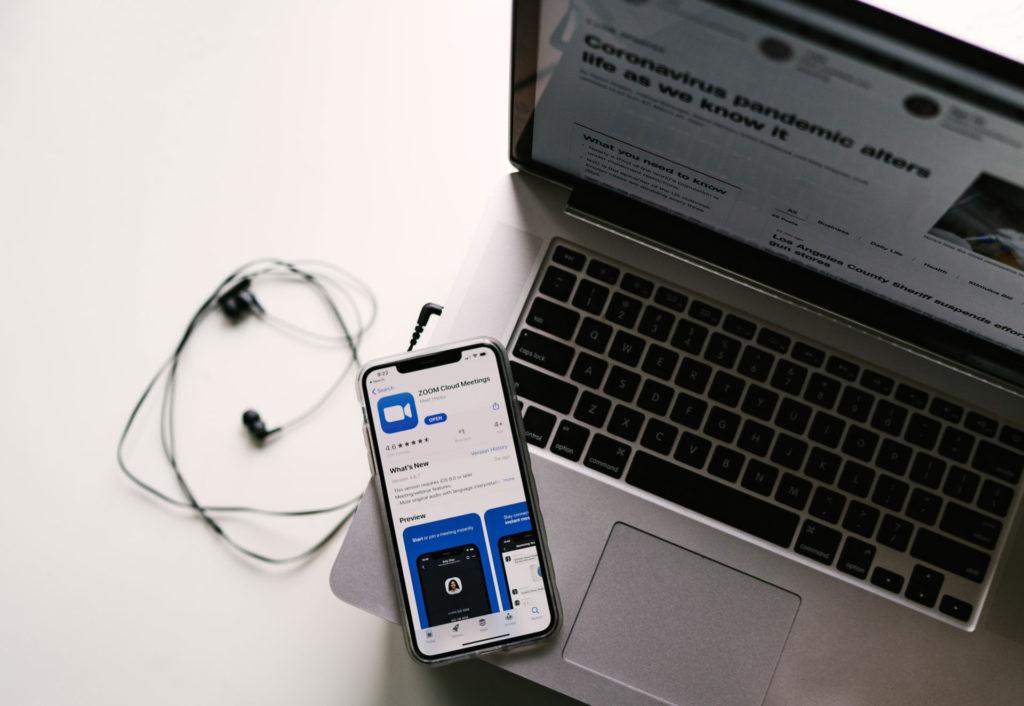 Kannettava tietokone ja älypuhelin, jonka näytöllä Zoom-sovelluksen sivu.
