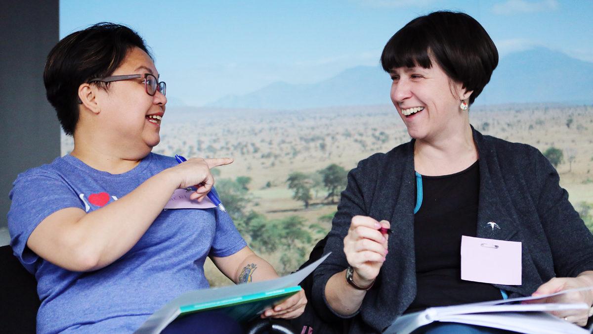 Kaksi hymyilevää naista keskustelee muistiinpanovihkot käsissään.