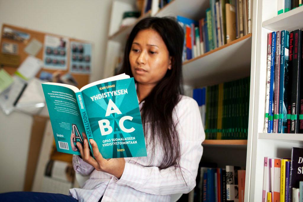 Nainen lukee kirjaa nimeltä Yhdistylsen ABC, Opas suomalaiseen yhdistystoimintaan.