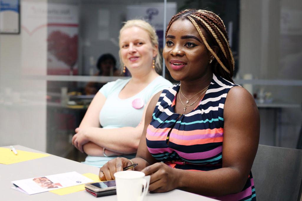 Kaksi hymyilevää naista istuu pöydän ääressä.