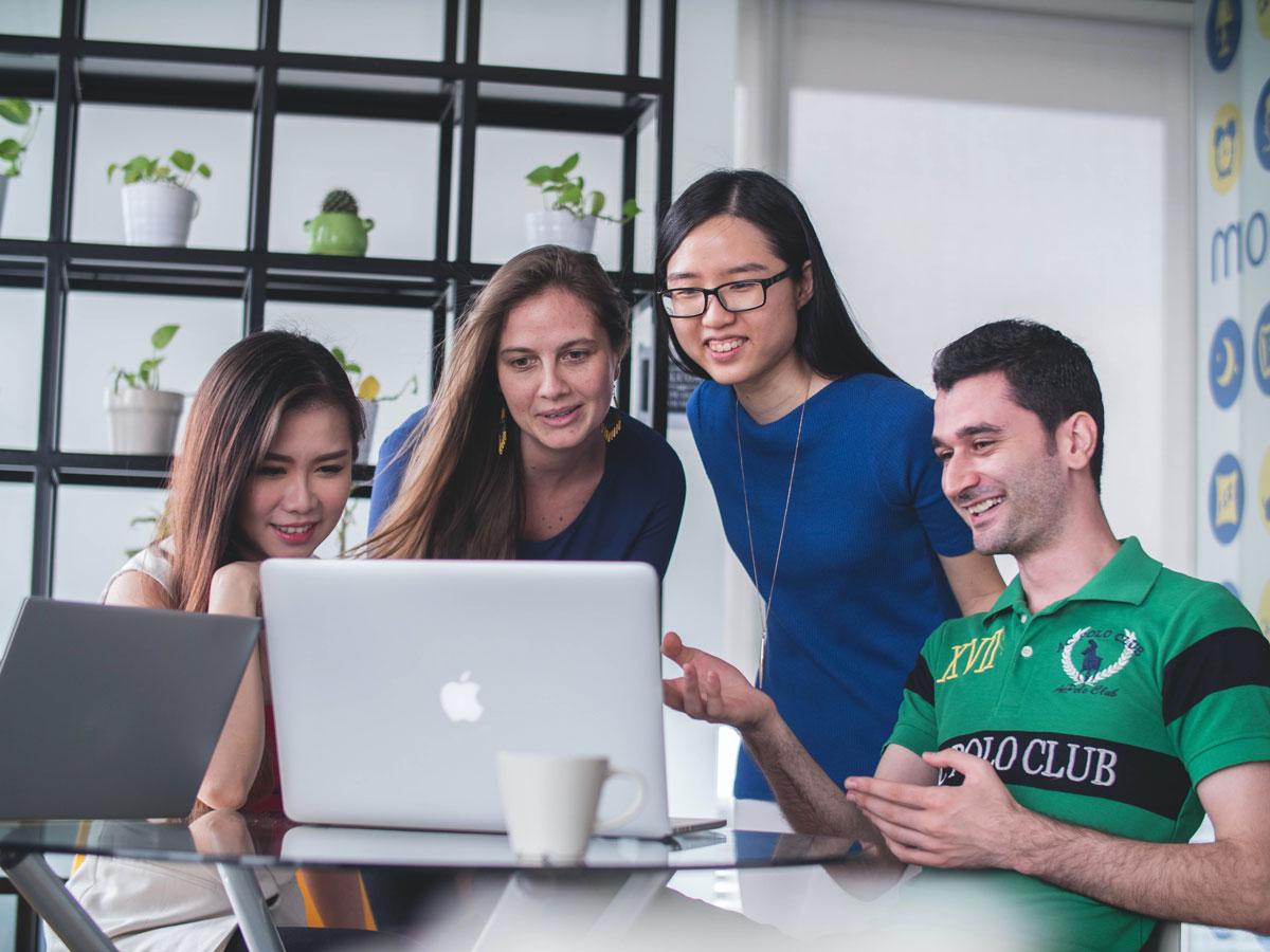 Neljä hymyilevää ihmistä on kumartunut katsomaan kiinnostuneena pöydällä olevan tietokoneen näyttöä.