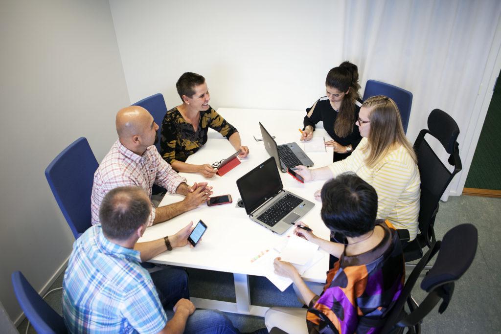 Kuusi ihmistä istuu pöydän ääressä ja keskustelee. Pöydällä on kannettavia tietokoneita.