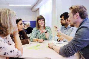 Ryhmä ihmisiä keskustelemassa pöydän ääressä.
