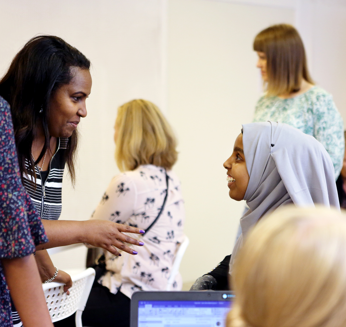 Kaksi naista keskustelemassa iloisesti koulutustapahtumassa
