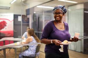Hymyilevä nainen kävelee toimistolla